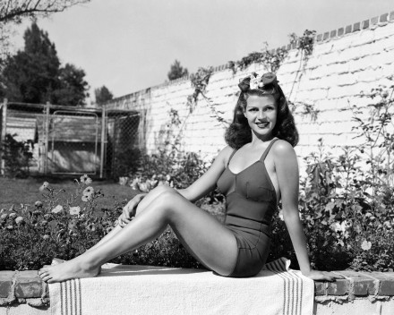1941: American film actress Rita Hayworth (1918 - 1987) sitting on a garden wall in a one-piece swimsuit.