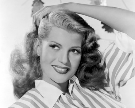 circa 1942: Portrait of American actor Rita Hayworth (1918 - 1987) pulling back her hair with one hand and wearing a striped shirt.