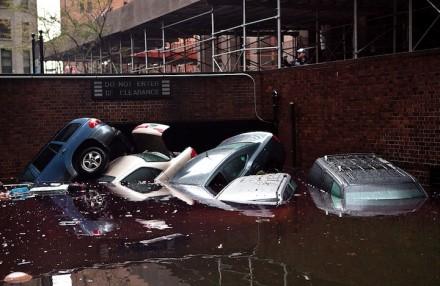 Carros flutuando em uma entrada de garagem inundada, em 30 de outubro, no distrito financeiro de   Nova York (Foto: Andrew Burton / Getty Images)