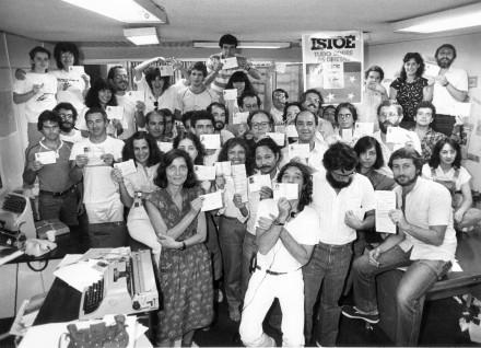 """Na """"IstoÉ"""", em novembro de 1983, com a redação exibindo seu título de eleitor (a capa da semana seria sobre as Diretas Já): Cida é a jovem sorridente bem no meio da foto, ao lado do rapaz de bigode (o jornalista Antônio Carlos Fon)"""