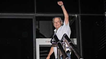 """Dirceu ergue desafiadoramente o punho, na tradicional saudação comunista, ao se entregar à Polícia Federal em novembro de 2013: exercendo o """"direito de espernear"""" (Foto: Eduardo Knapp/Folhapress)"""